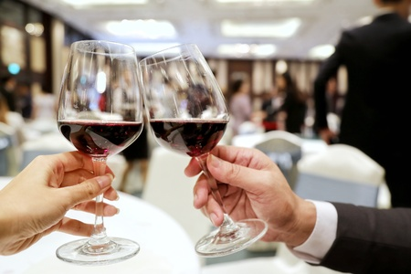 two persons clinking glasses of rich red wine in a party. Concept of making new friend, joining party, drink don't drive Standard-Bild