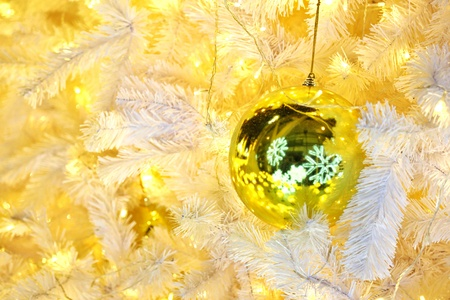 Golden Ball Bauble Reflecting Snow Flakes Decorated on Christmas tree