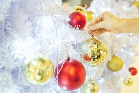 Closeup image of a hand decorating white snow Christmas tree with gold sparkling glitter baubles disco crystal ball style. Concept and idea of celebrating Christmas holidays