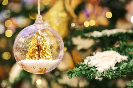 A little golden Christmas tree in the crystal clear bauble ball hangs as a decoration with blur background of Christmas tree with some snow on its leaf.