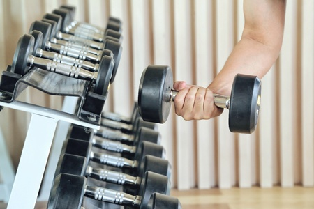 Close up of man holding weight in gym. fitness concept. holding dumbbell in fitness center. concept of healthy