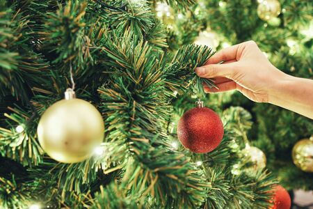Closeup image of a hand decorating Christmas tree with red sparkling glitter baubles. Concept and idea of celebrating Christmas holidays