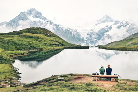 Romantic couple on a bench by the mountain lake