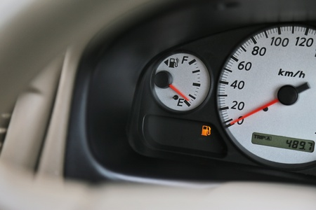 Driving car with digital oil gasoline level sign on the panel dashboard indicates that oil fuel is running low. Foto de archivo