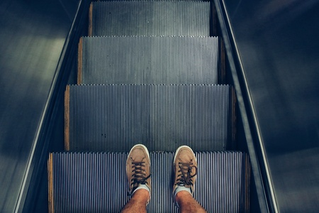Selfie of feet in sneaker shoes on escalator steps, top view in vintage style
