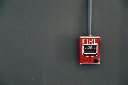A red fire alarm pull station on the dark grey wall.