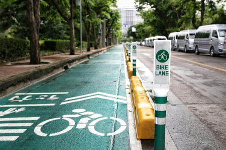 Focus bike lane sign pole in with green tree background. Banco de Imagens
