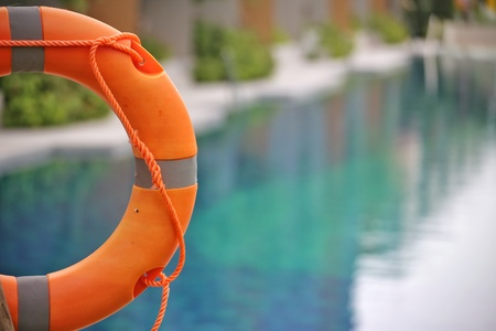 Lifebuoy,Life preserver,Life ring,Life belt  hanging at the public swimming pool in the blur background. To show concept of safety.