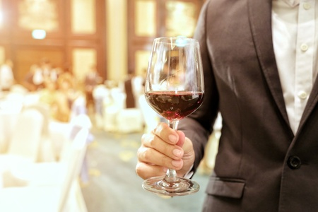 Close of of business man wearing suit holding a glass of wine in the company party with ray yellow light in the background. Concept and idea of business success, celebration party.