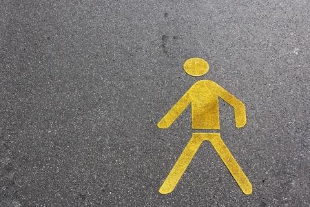 pedestrian lane sign in yellow on the asphalt ground