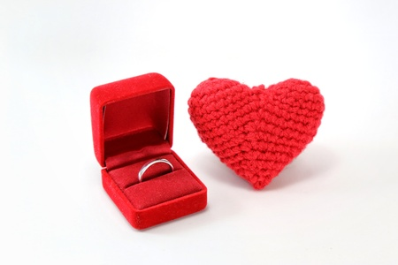 Red crocheted heart with wedding ring in a box on isolated white background. Valentines Day. Symbol of love.