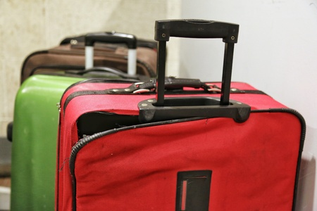 Red broken traveling luggage, crack and torn at the corner with other baggage in background, at the airport. Need to be repaired and claimed the airline Imagens