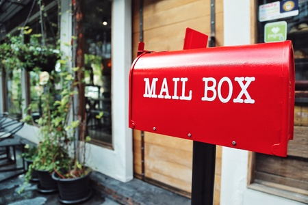 Red mail box in front of a house Concept of e commerce Nowadays Post office mainly provide shipping service