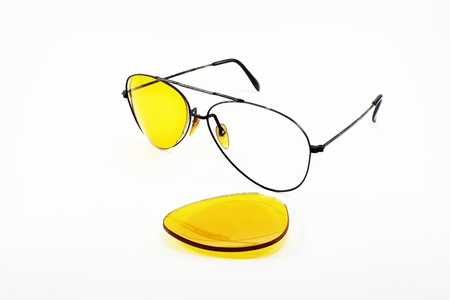 Broken yellow sunglasses lens on white background