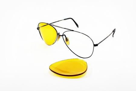Broken yellow sunglasses lens on white background