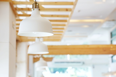 Close up of beautiful white simply modern ceiling lamps in restaurant with blurry background copy space.