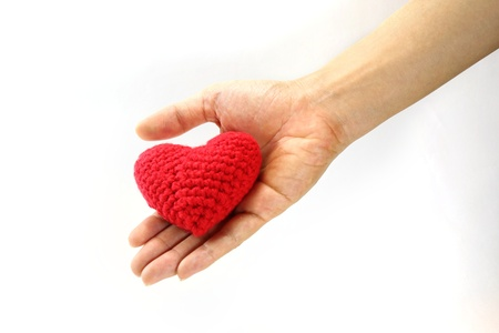 Woman hand giving red crocheted heart. Valentine's Day. Symbol of love. Standard-Bild