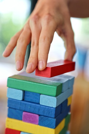 Close-up of asian woman's hand playing colorful wood blocks stack game in morning light , playing and learning background concept Standard-Bild