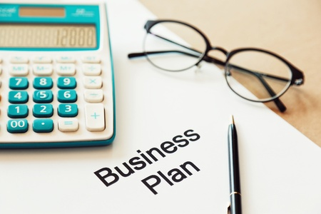 Working on business plan and calculating cost with pen and eye glasses. Archivio Fotografico