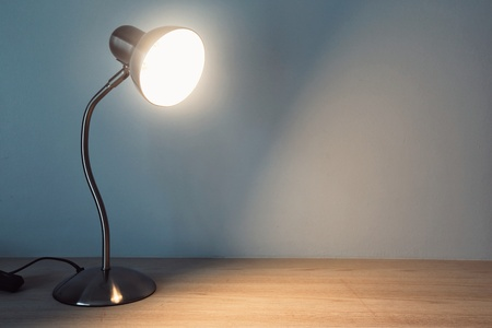 table lamp with light-on on the wooden table in vintage style. Archivio Fotografico