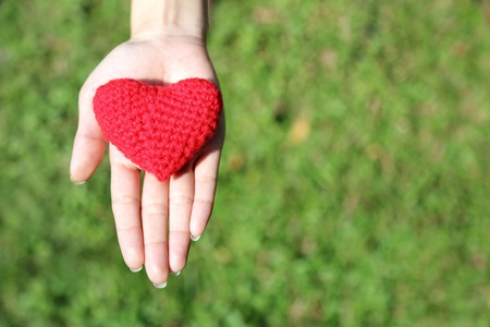 Woman hand giving red hand-made crocheted heart with green grass background and copy space. Valentine's Day. Symbol of love.