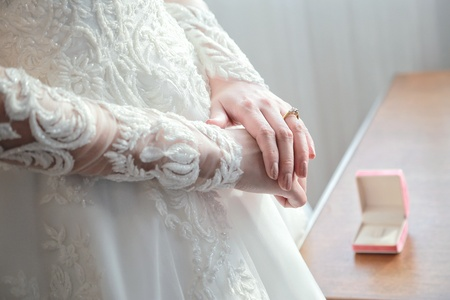 Womens hands on a white wedding dress. show her wedding ring with box in background.