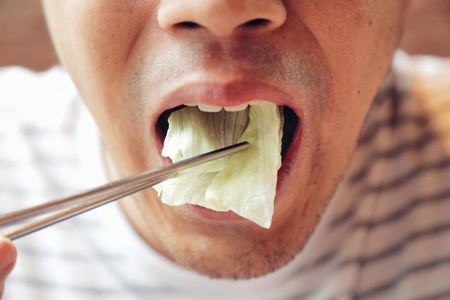 Closeup Asian male eating fresh vegetable food,Napa cabbage, in Chinese style with chopstick. Show concept and idea of healthy. Banco de Imagens