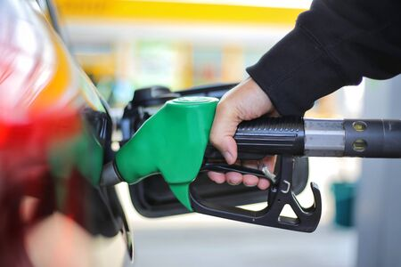 Close up hand holding green gasoline fuel nozzle and being fill gas tank of black car in gas station Concept of Global Fossil Fuel Consumption.  Replace by alternative energy in near the near future