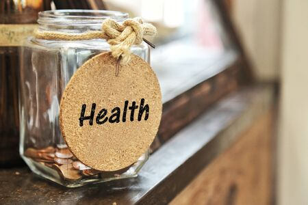 Vintage retro glass jar with hemp rope tie health tag and few coins inside on wood counter concept of save money for health care maintenance improvement prevention diagnosis treatment physical mental Standard-Bild