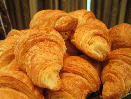 breadbasket: pile of croissants in on shelf in bakery or bakers shop Stock Photo