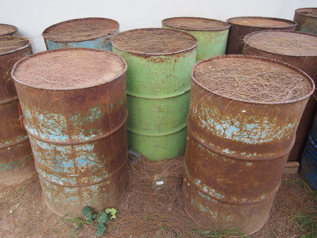 abandoned corroding rusty oil barrels on the ground Stok Fotoğraf