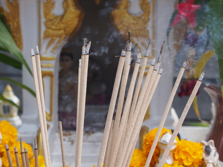 burning incense sticks on blurred background of spirit house with waving smoking Stock Photo