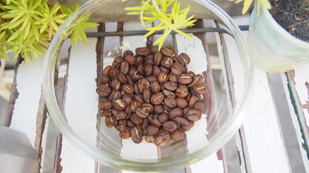 coffee beans heap in glass heap on wooden table, top view