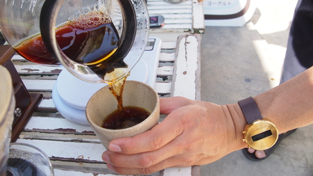 hand drip coffee, barista pouring hot water over roasted grinded coffee powder making drip brew coffee