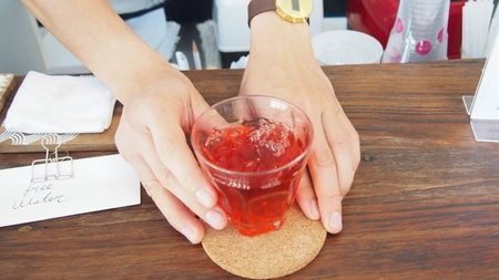 close up of hand serves ice rose tea drink at counter bar in cafe