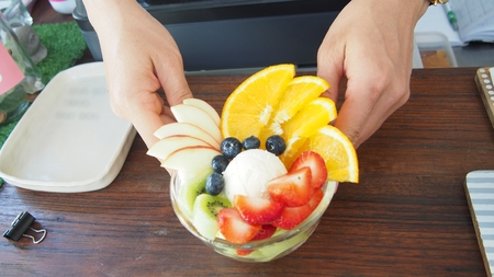 close up of hand serves ice cream fruit salad at counter bar in cafe Stock Photo