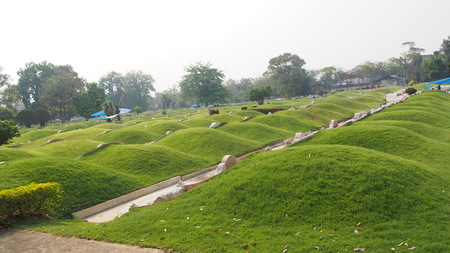 Chinese cemetery, mound and slope grass graves of chinese graveyard Stock Photo