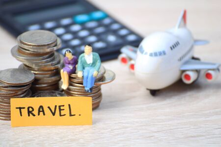 Miniature people love couple sit on coins with plane for tour around world,Concept for those who succeed from saving and investing. Archivio Fotografico