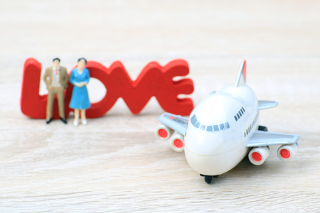 Miniature people love couple stand with plane for tour around world,Concept for those who succeed from saving and investing. Archivio Fotografico
