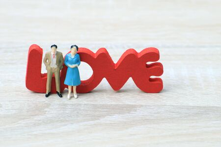 Miniature people love couple stand with love symbol