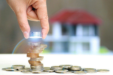 Woman hand put stack coins, Save money for real estate To prepare for a home purchase and financial plan or loan for the future concept.
