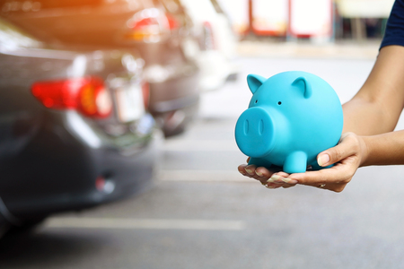 woman holding blue piggy bank with standing near the car for save money to buy vehicle & insurance