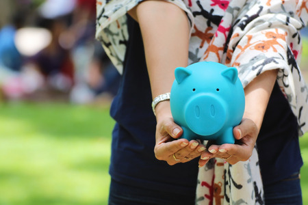 Female hand holding a blue piggy bank, ideas of financial investment or Banking