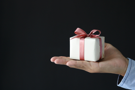 male hands holding a small gift wrapped with pink ribbon. Small gift in the hands of a man on black background.