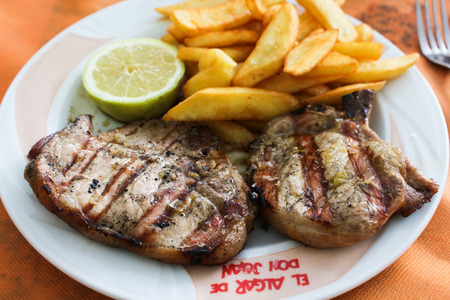 grilled pork chop: juicy grilled pork chop and french fries Stock Photo