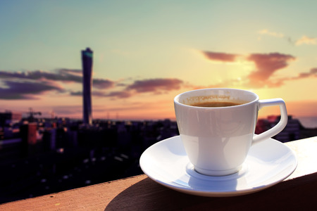 Morning cup of coffee with cityscape background at sunrise