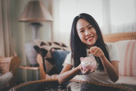 Happy young woman and hand putting coin into piggy bank, Finance or Savings concept.