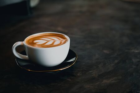 Coffee cup with latte art on old table