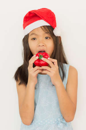 eating fruits: A girl wearing a red hat Wearing a blue shirtThey will eat the fruit on the background isolation.