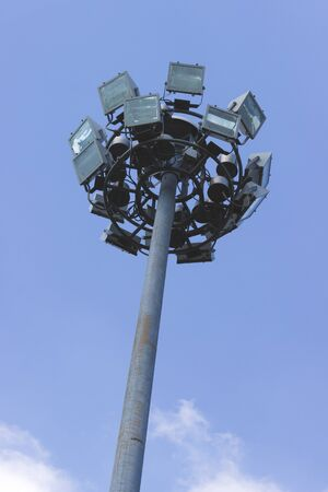 Stadium light pole in blue sky.